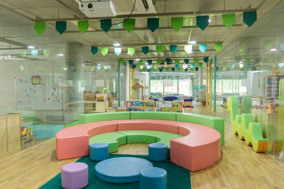 A professional image of the interior of a childcare centre, featuring a round green, red and blue couch in the front with various toys and play equipment in the background