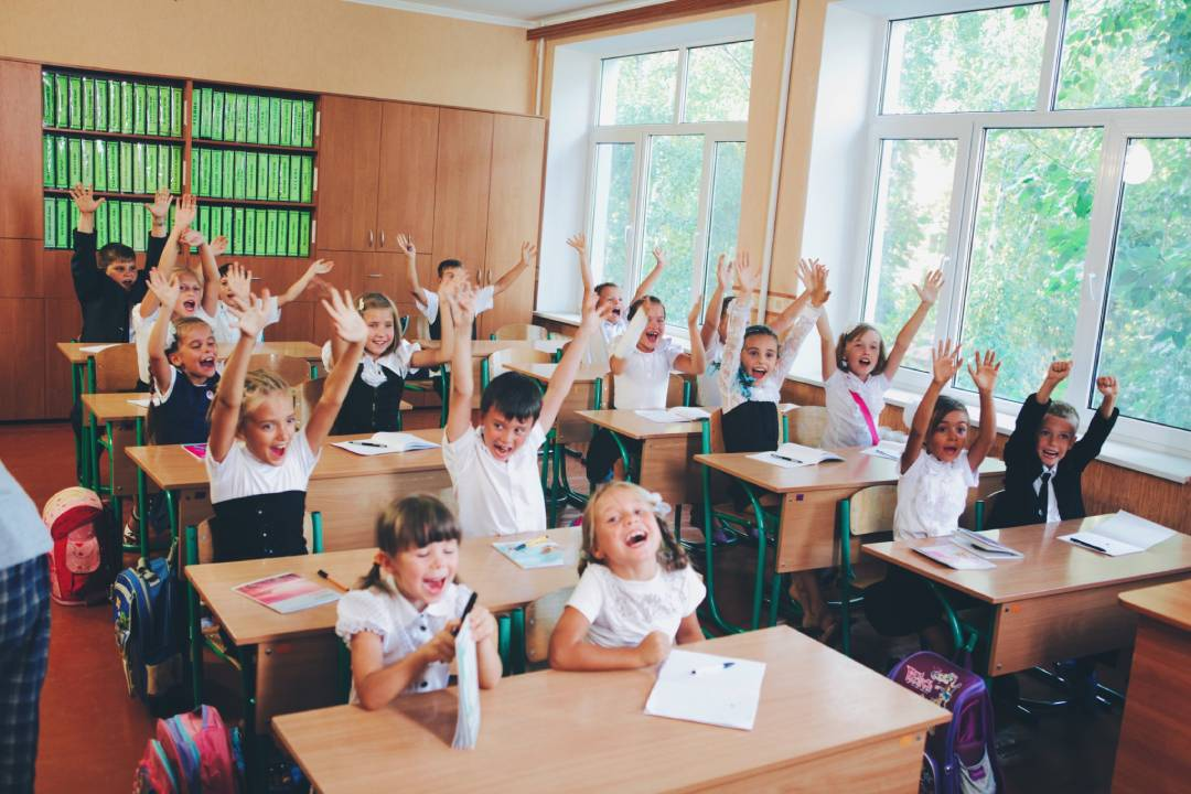 A classroom of young children cheering with their hands up