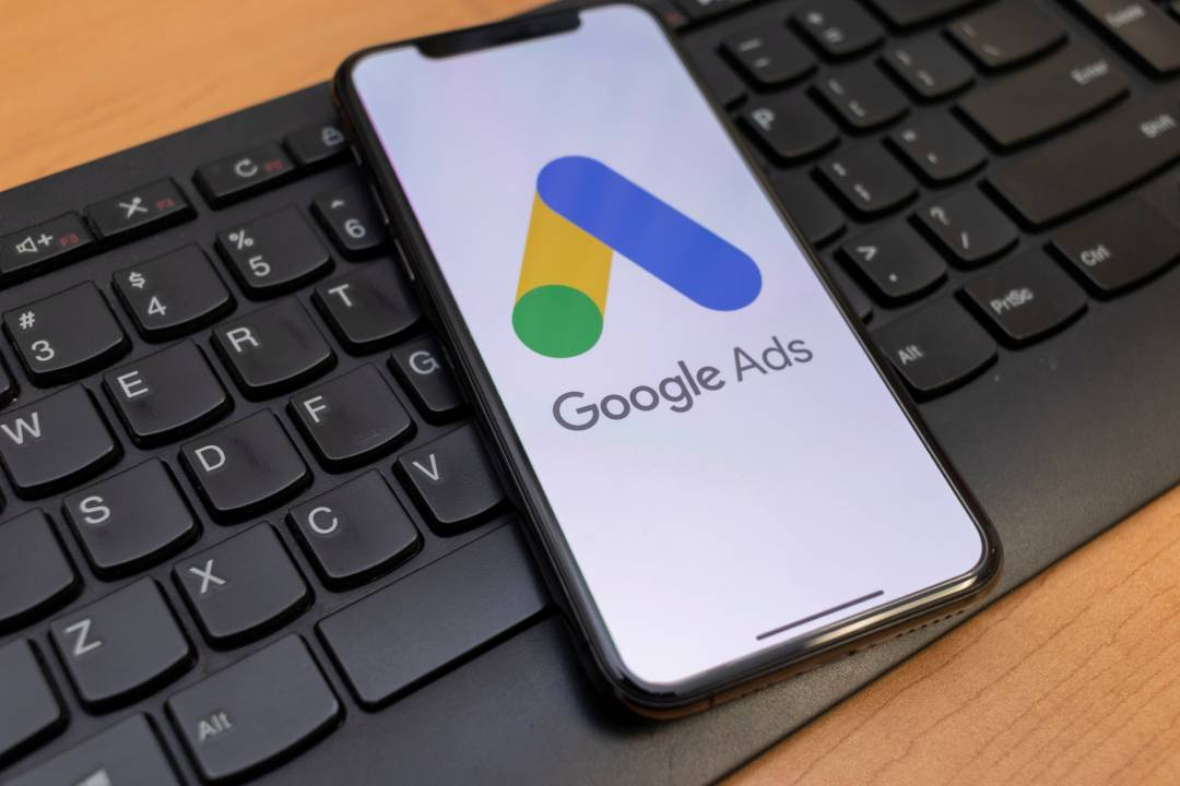An Apple Iphone displaying the Google Ads logo on screen sits on top of a black keyboard.